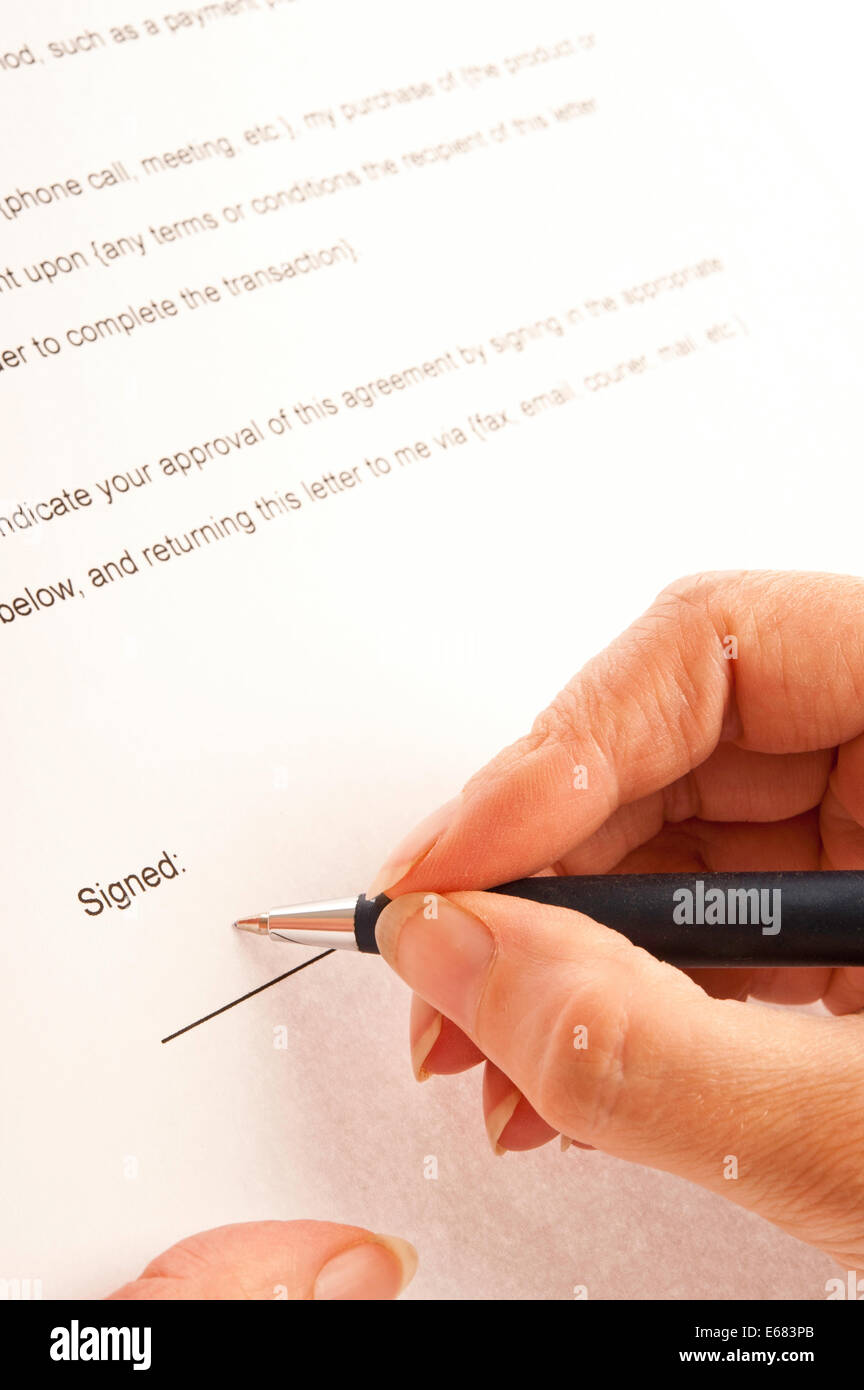 woman signing a contract - Stock Image
