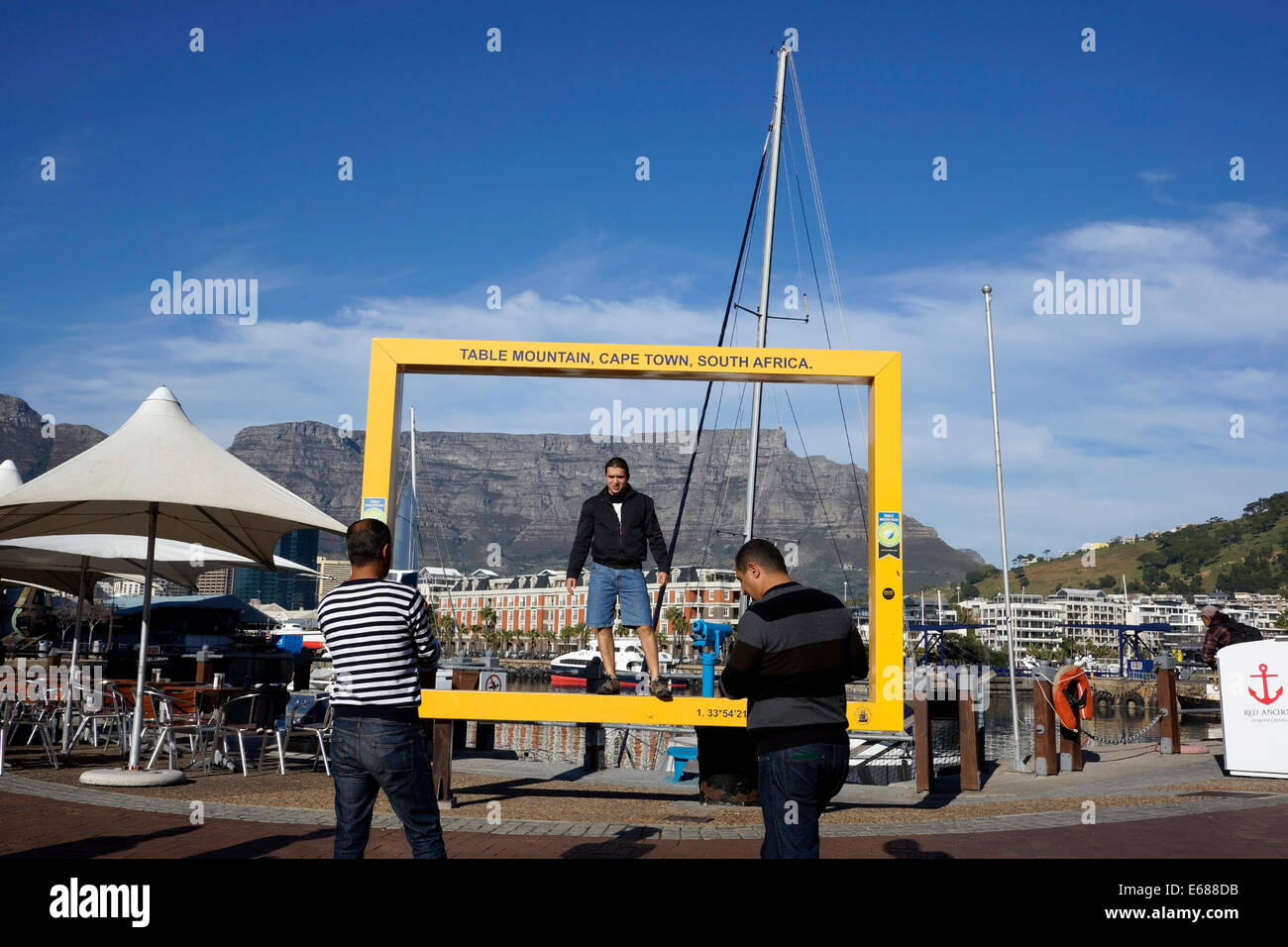 Tourists posing for pictures with Table Mountain in the background at the Victoria & Alfred Waterfront, Cape - Stock Image