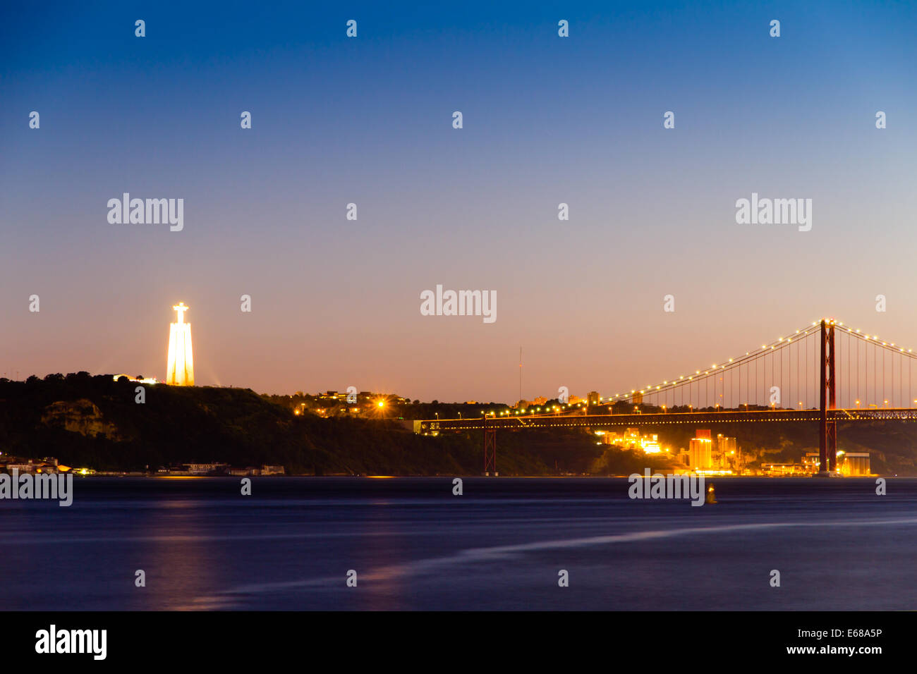 The Christ the King statue (Portuguese: Cristo Rei) and partial view of the 25 de Abril Bridge (Ponte 25 de Abril) Stock Photo