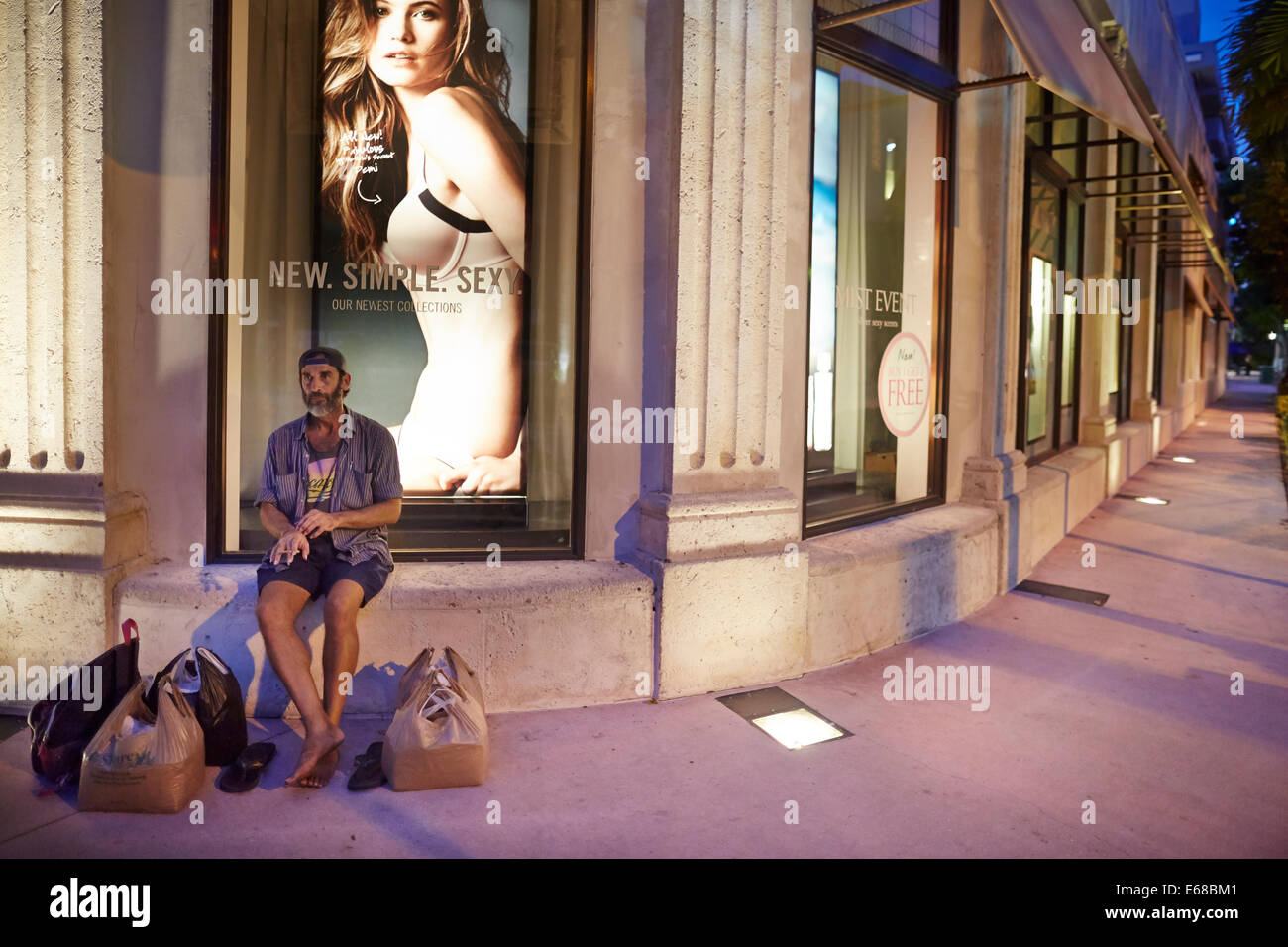 Lincoln Road Mall in the evening a lone male sits outside Victoria Secrets store surrounded by shopping bags - Stock Image