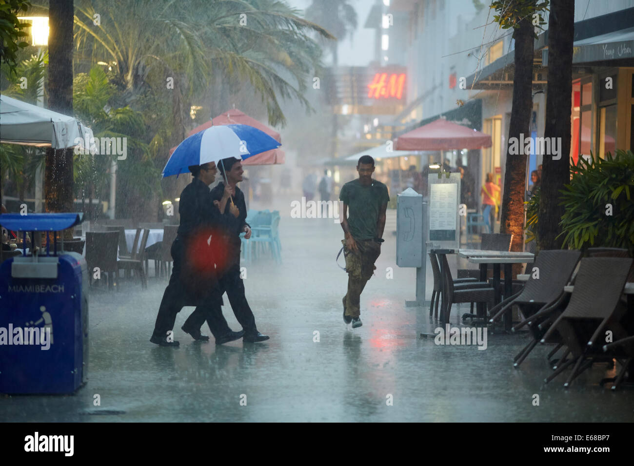 Picture of two waiters sharing an umbrella to serve the public in the pouring rain - Stock Image