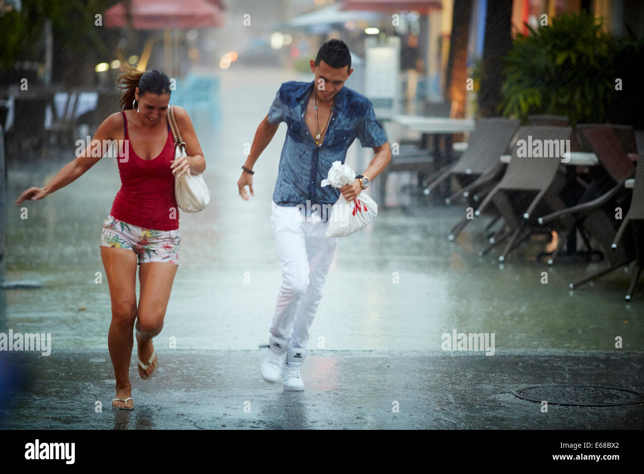 A picture boy girl couple run through the street in the pouring rain - Stock Image