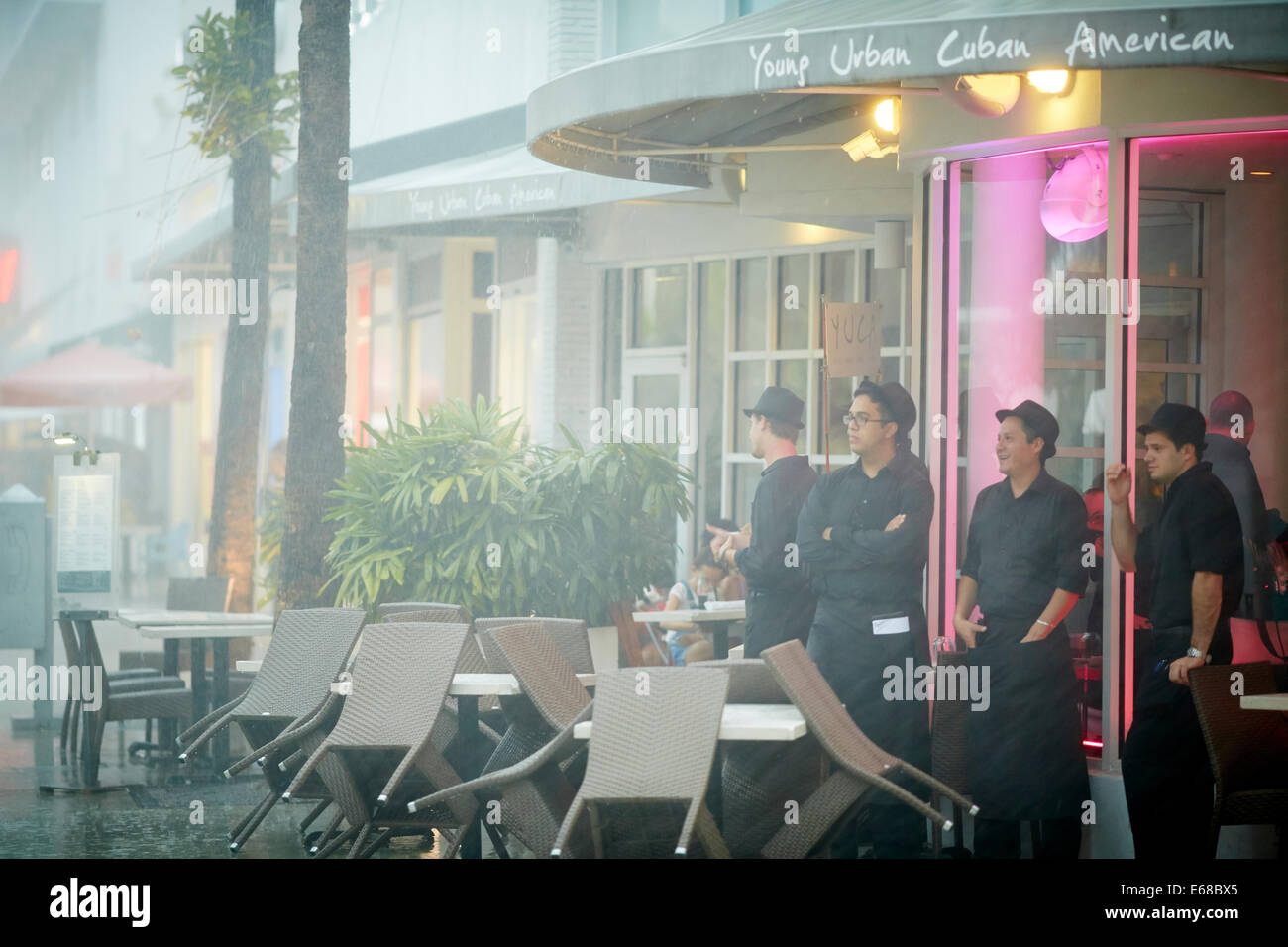 Waiters stood outside the restaurant waiting for the rain to pass over - Stock Image