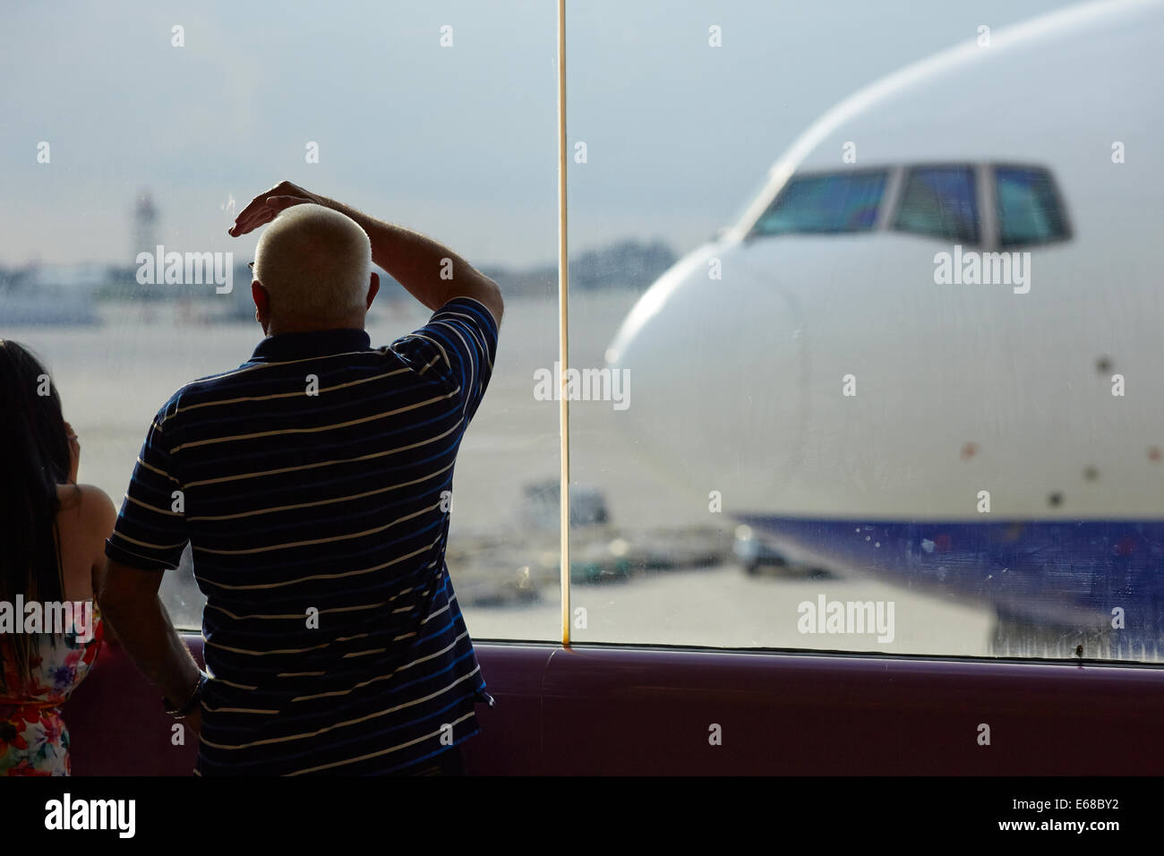 Passenger looking through the glass at Ransaero Airlines plane Beoing 777 - Stock Image