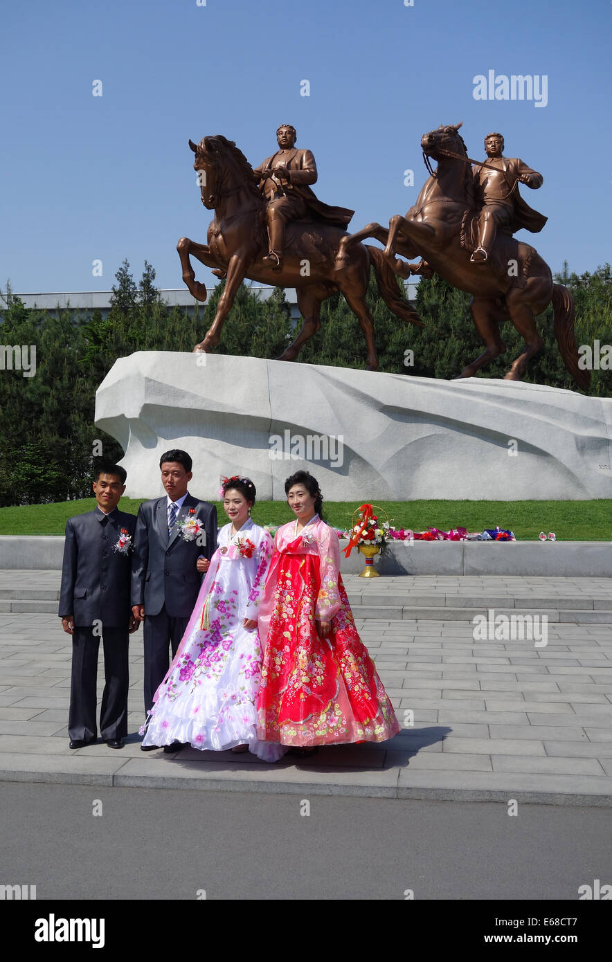 Wedding group, Bride and Groom in front of statue of Great Leaders Kim Il Sung and Kim Jong Il, Pyongyang, North - Stock Image