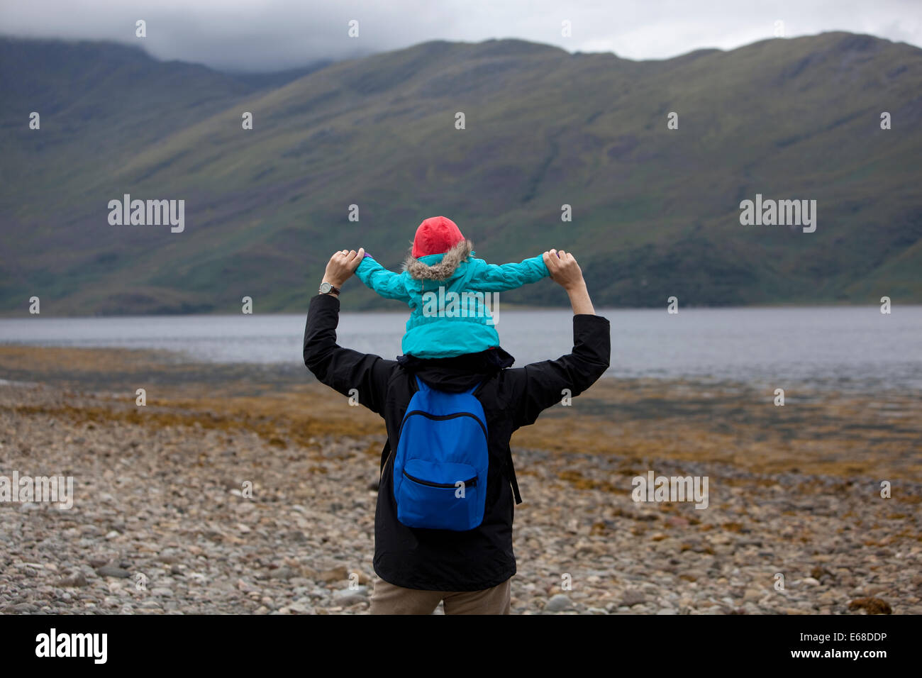 Father with child on his shoulders, walking along a pebble beach in Scotland. - Stock Image