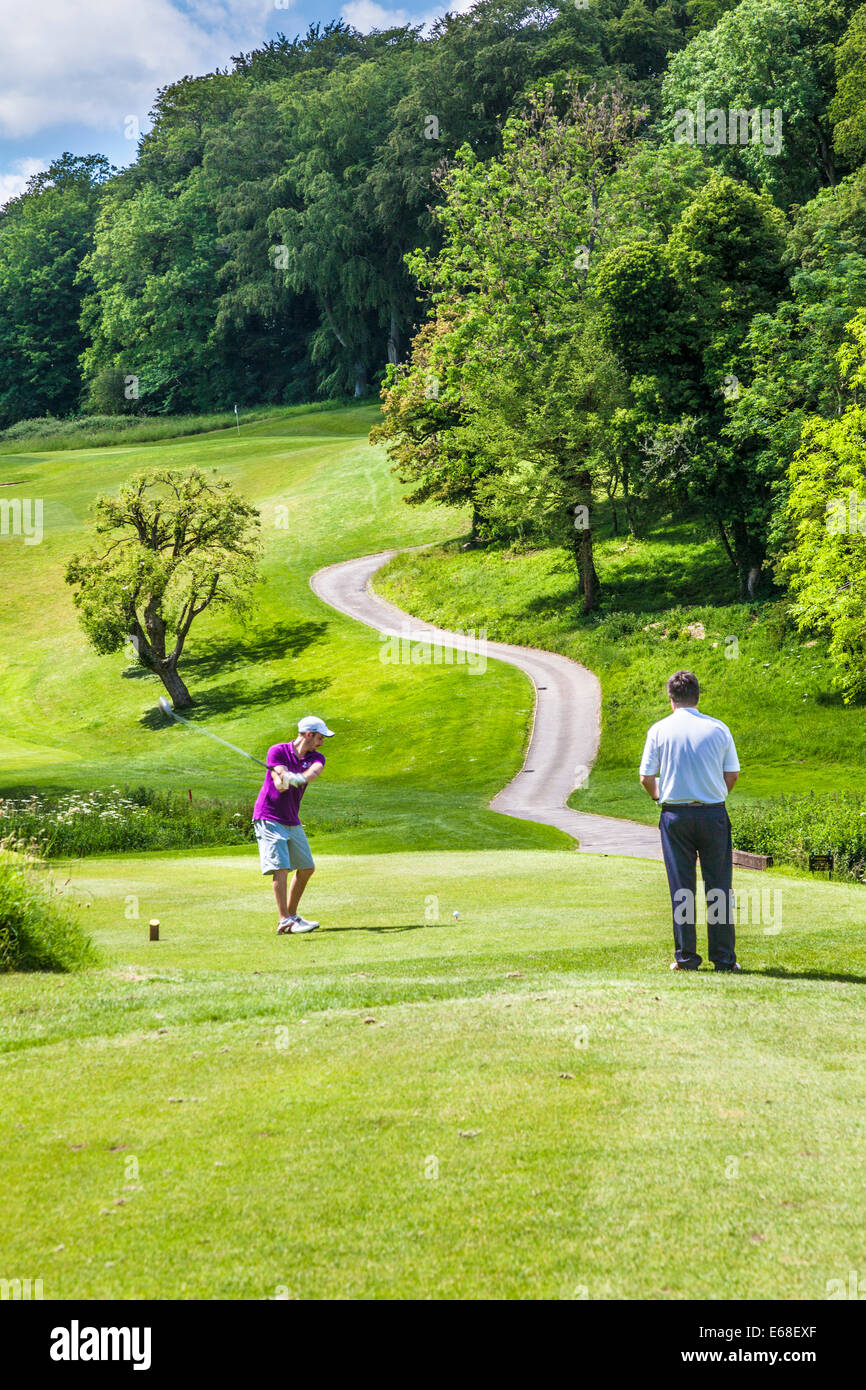 Golfer teeing off whilst another watches. - Stock Image