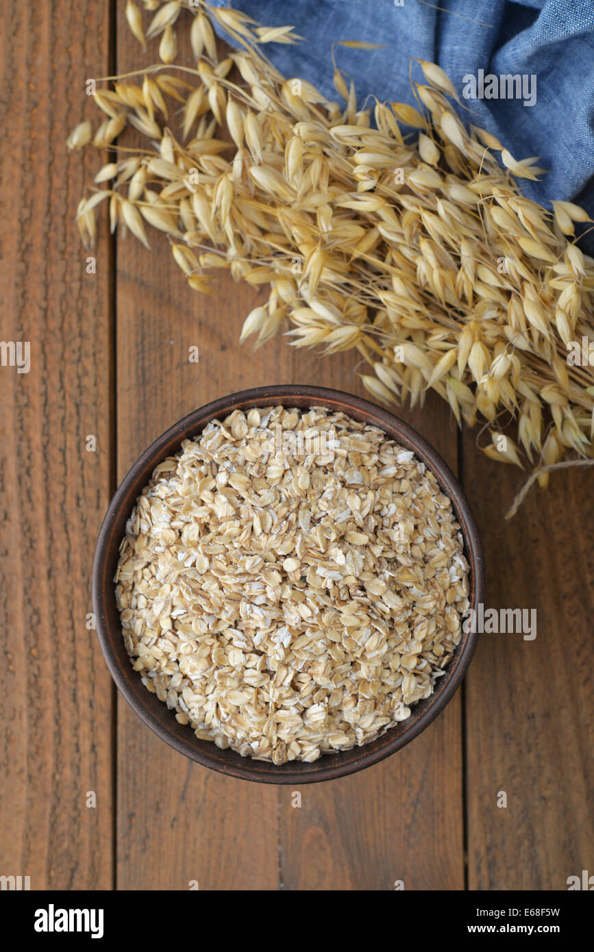 Oatflakes in a bowl on wooden background Stock Photo
