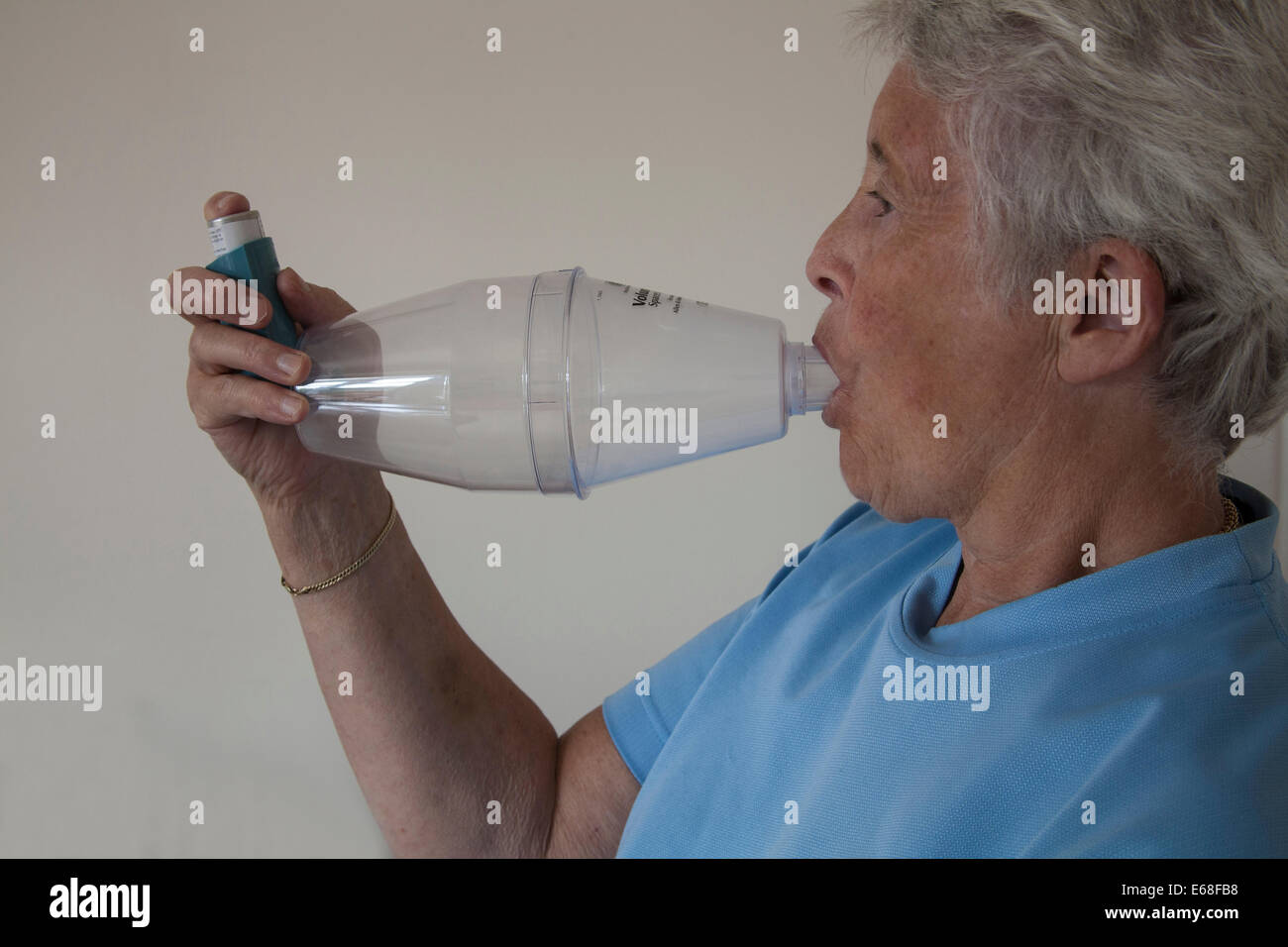 Elderly asthmatic woman using a Volumatic spacer device for Ventolin inhaling - Stock Image