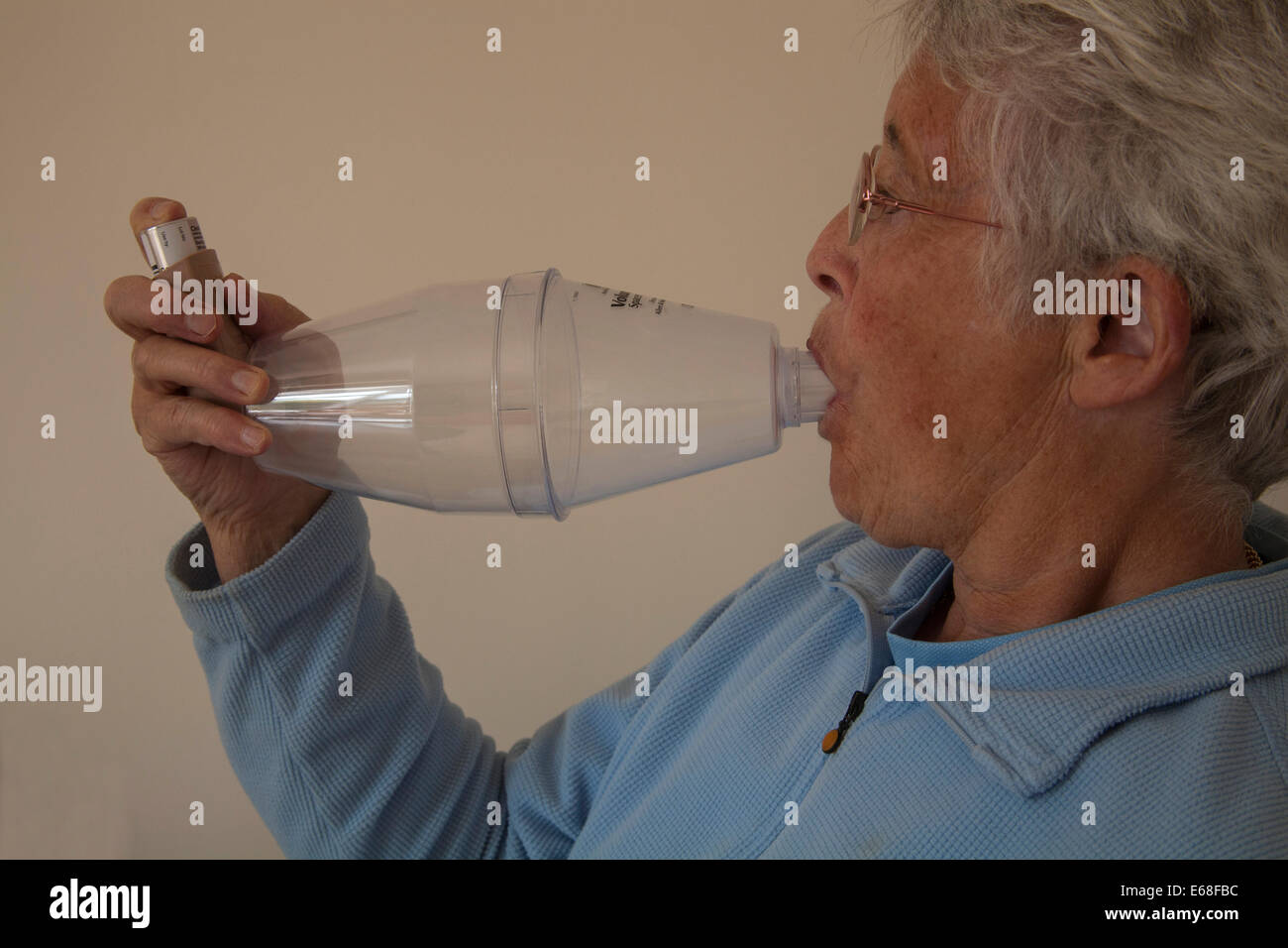 Elderly asthmatic woman using a Volumatic spacer device for steroid inhaler Stock Photo