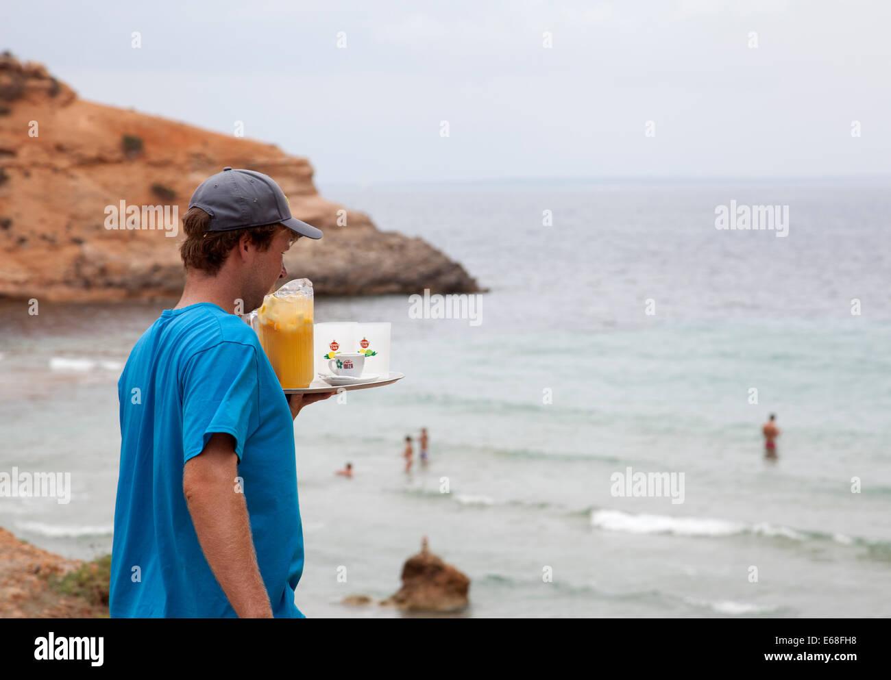 Waiter Taking Jug of Drinks onto Sa Caleta Beach in Ibiza - Stock Image
