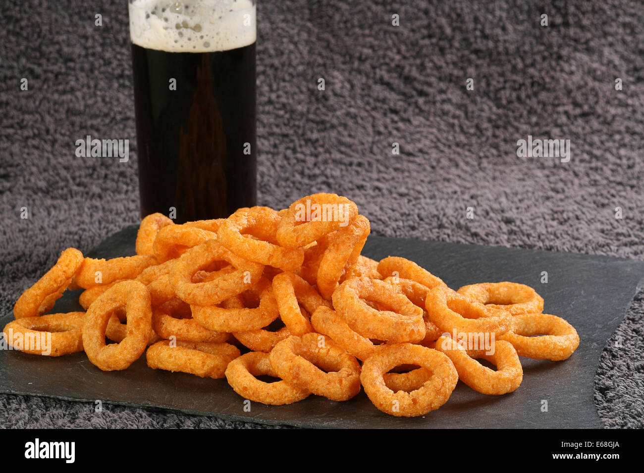 pile of onion flavoured crispy snacks wit a glass of beer - Stock Image