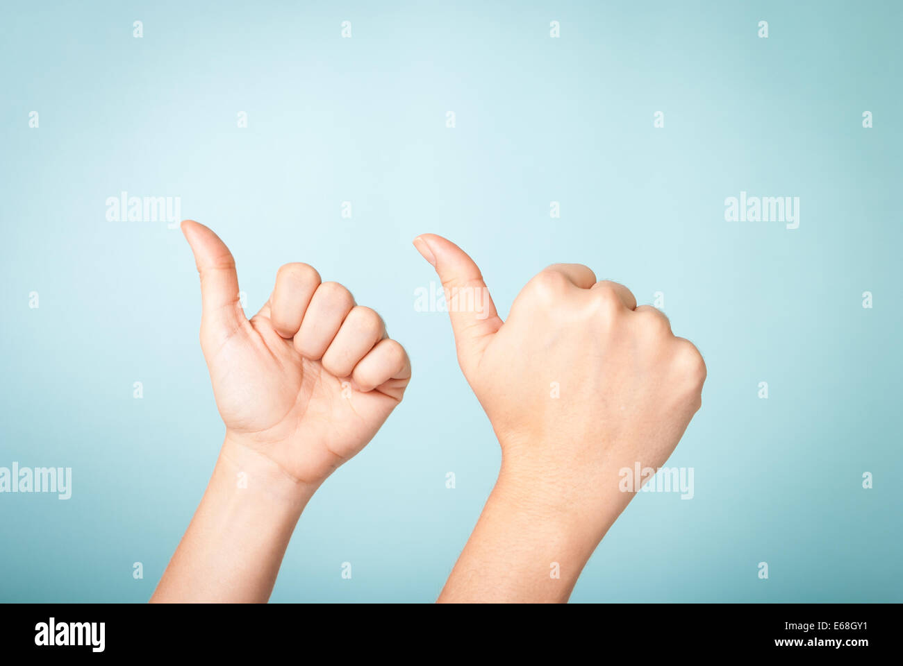 Two hands up making thumbs up gesture on blue background - Stock Image