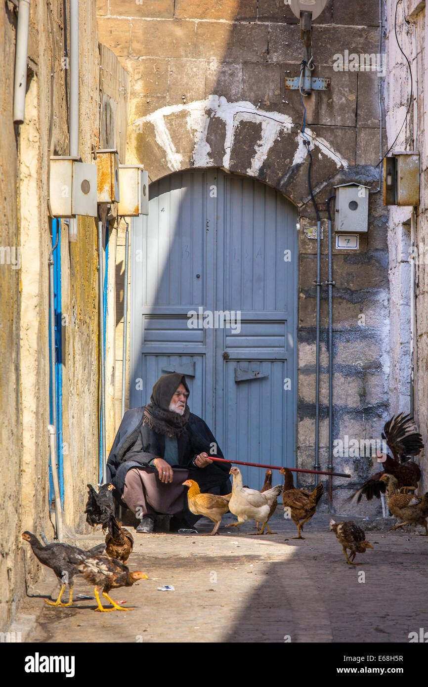 An old Kurdish-Turkish man, sitting in an alley of the old city of Sanliurfa, also known as Urfa, Southeastern Anatolia, - Stock Image