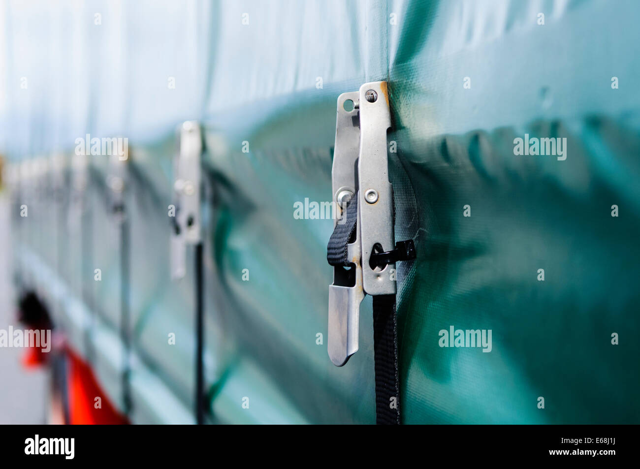 Tie-down straps and shackles on a curtain-sided trailer (Tautliner) - Stock Image