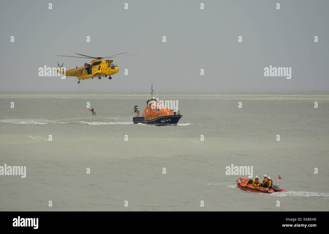 A Royal Air Force Sea King helicopter demonstrates one of its crew being lowered on to the Eastbourne lifeboat at - Stock Image