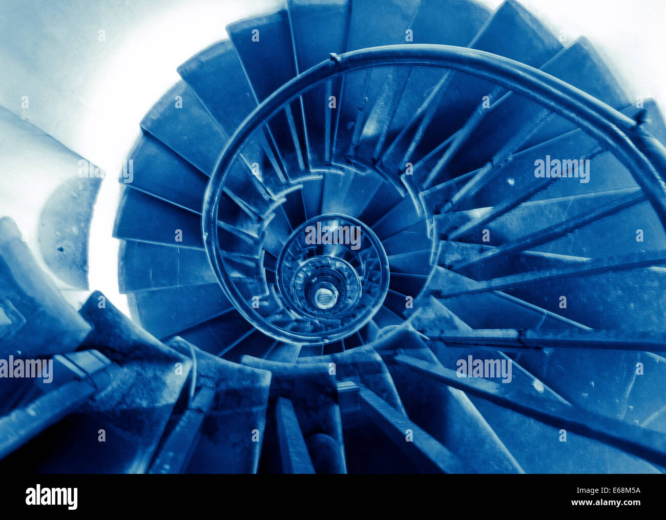 A spiral staircase bathed in blue light creates an interesting abstract image - Stock Image