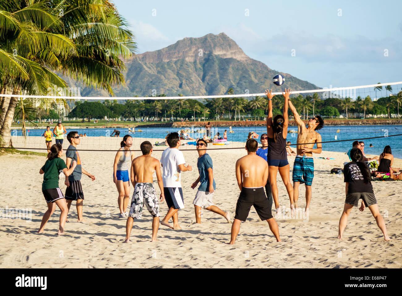 Hawaii Hawaiian Honolulu Ala Moana Beach State Regional Park volleyball game recreation sand Asian student playing Stock Photo