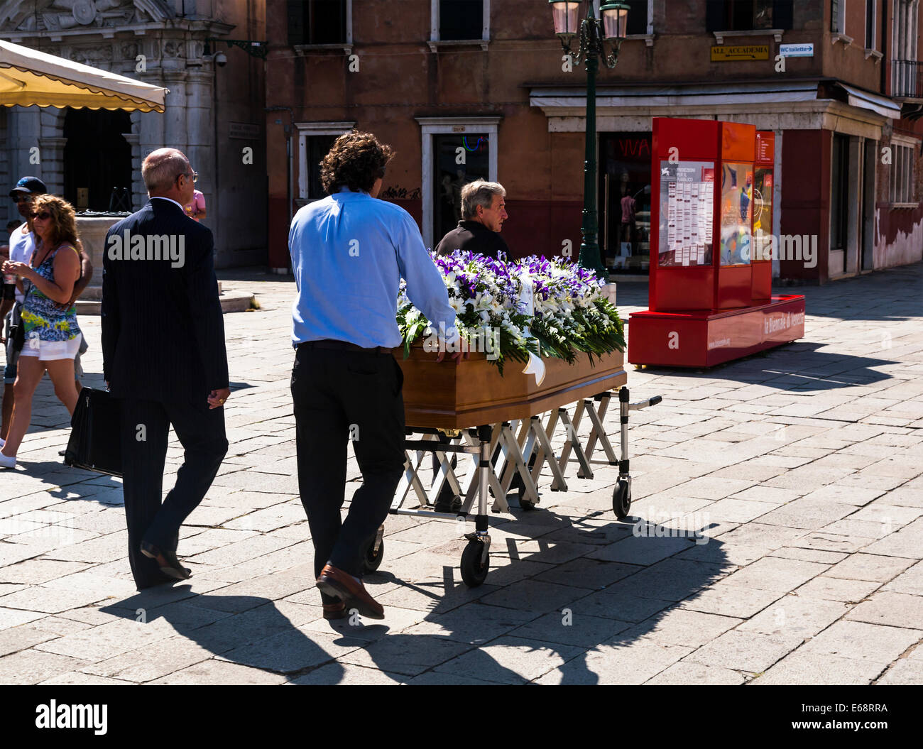 Funeral in Venice  with the coffin being pushed through the streets on a trolley, Veneto Italy. - Stock Image