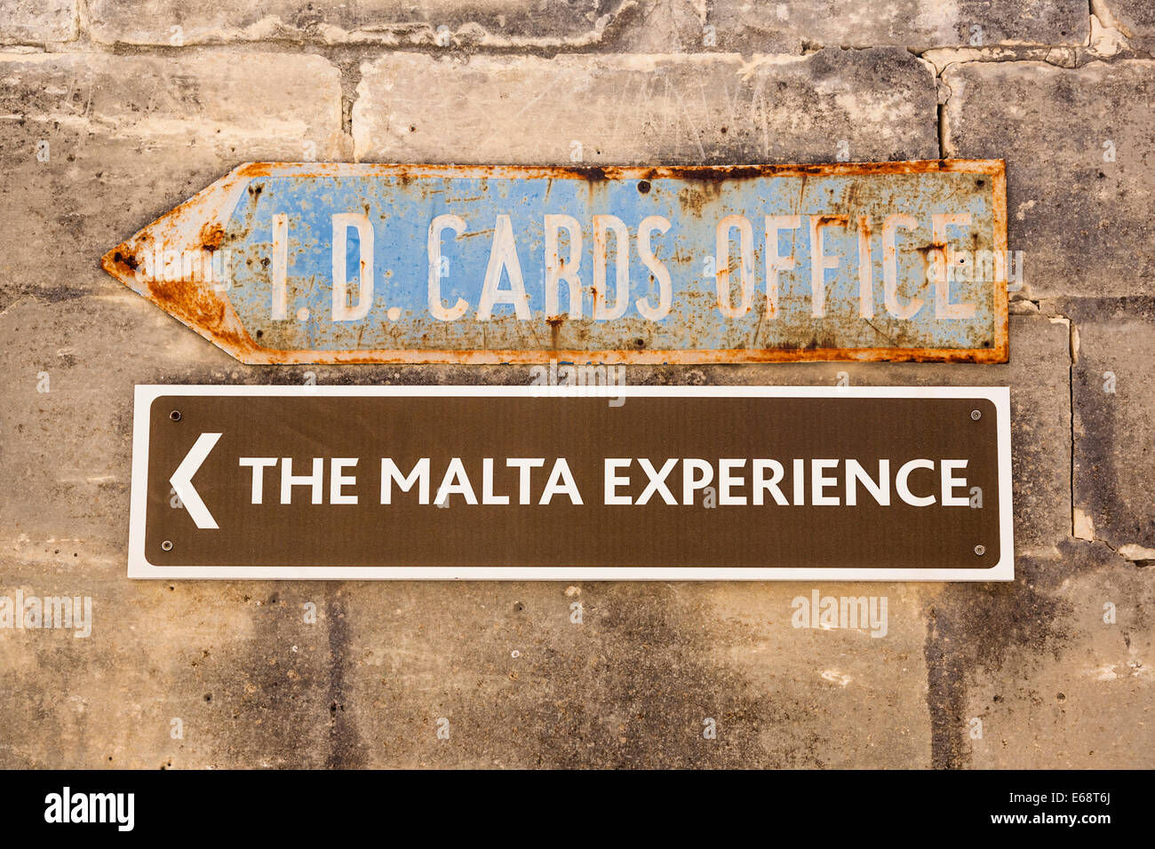 An old ID cards office sign from World War II on a Maltese wall above another sign for the Malta Experience, Malta. - Stock Image