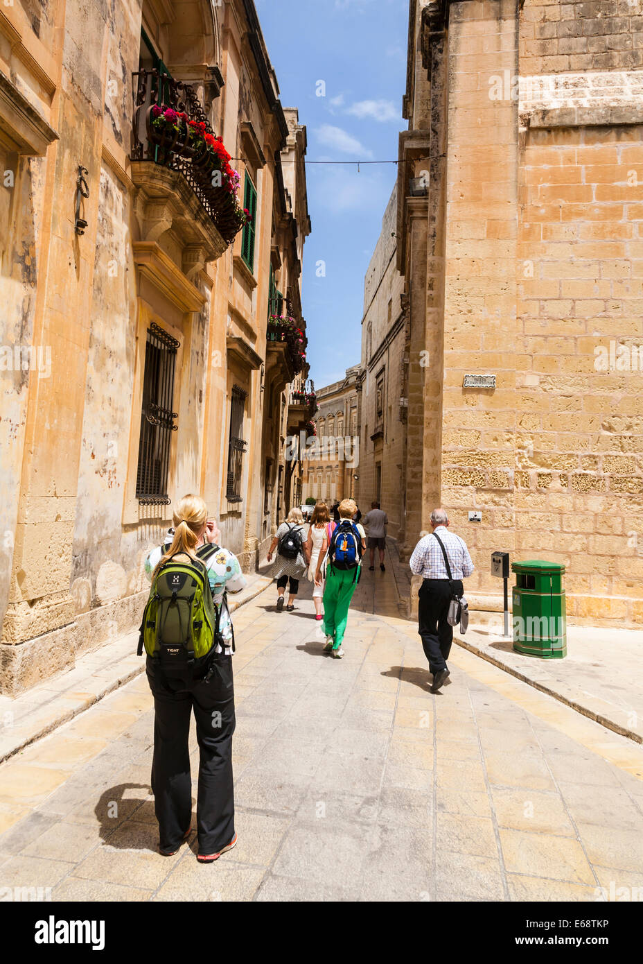 A group of tourists heading down one of Mdina's narrow streets, Malta. - Stock Image