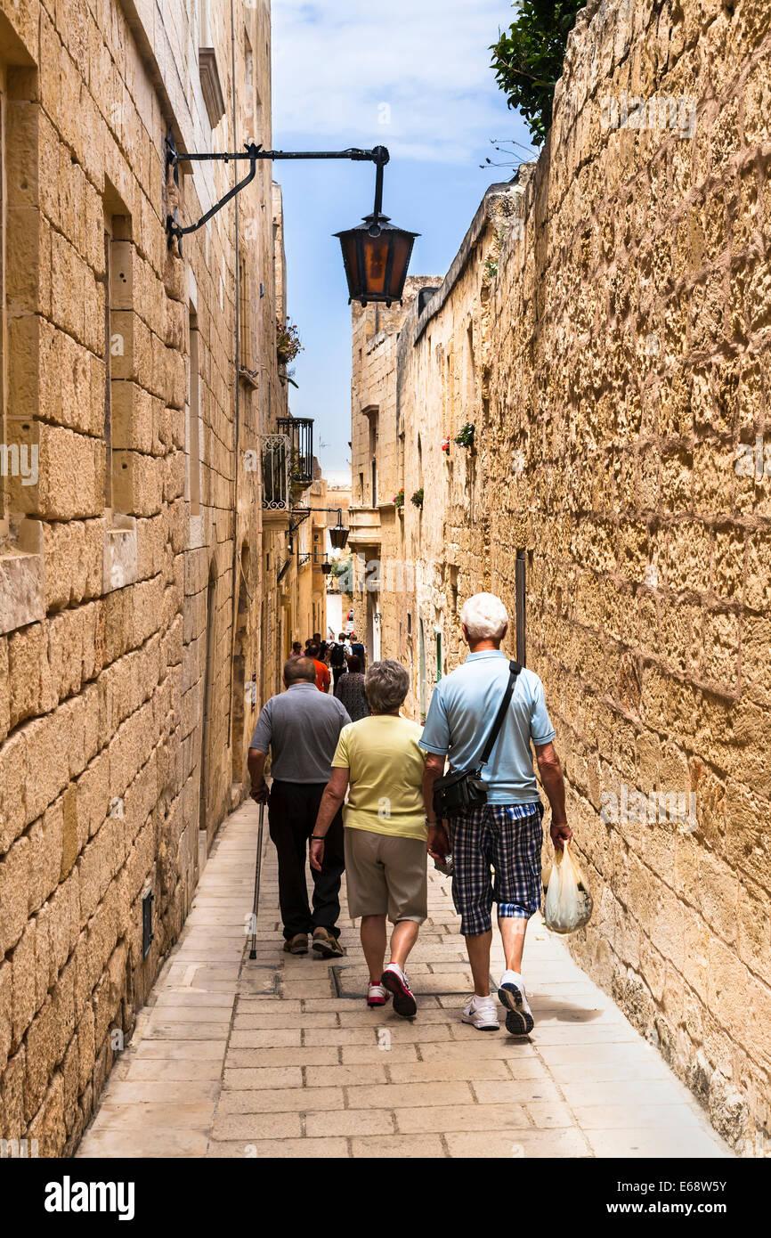Tourists walking down one of Mdina's narrow medieval streets, Mdina, Malta. - Stock Image