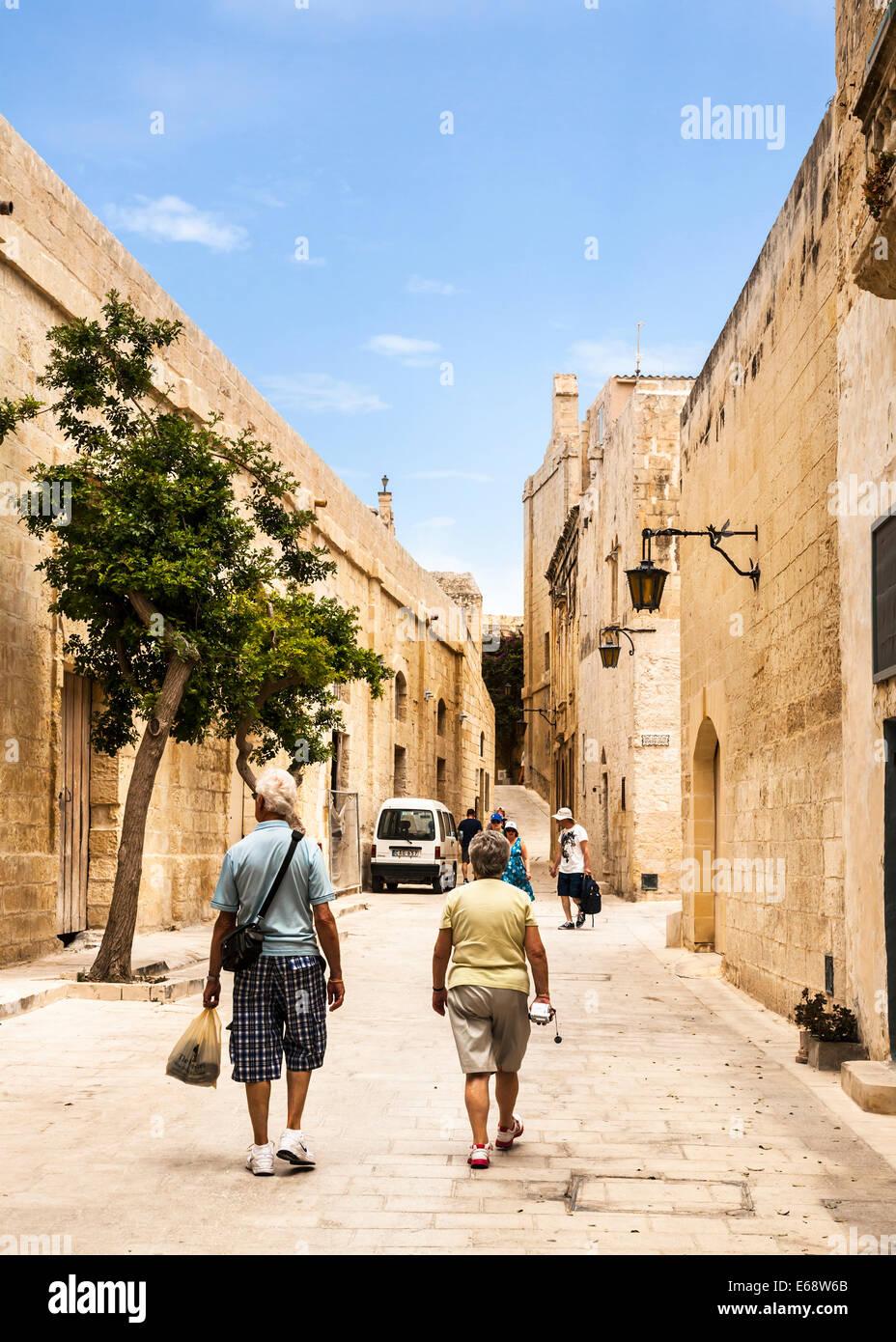 Tourists walking along Mdina's narrow medieval streets, Mdina, Malta. - Stock Image