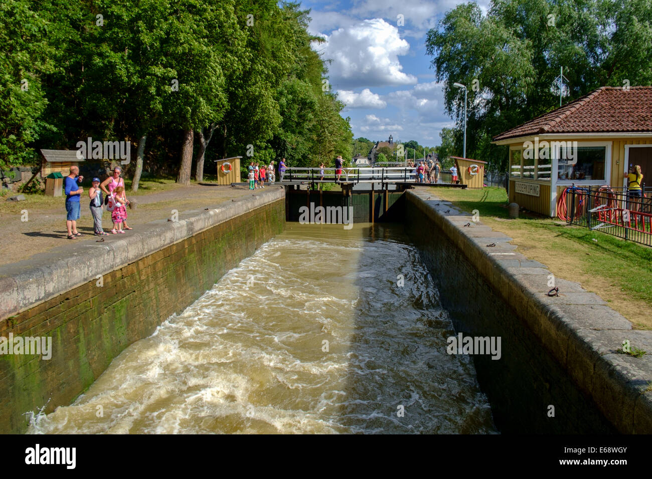 Tourists watch the water level rise in a lock at Gota Canal in Soderkoping Stock Photo