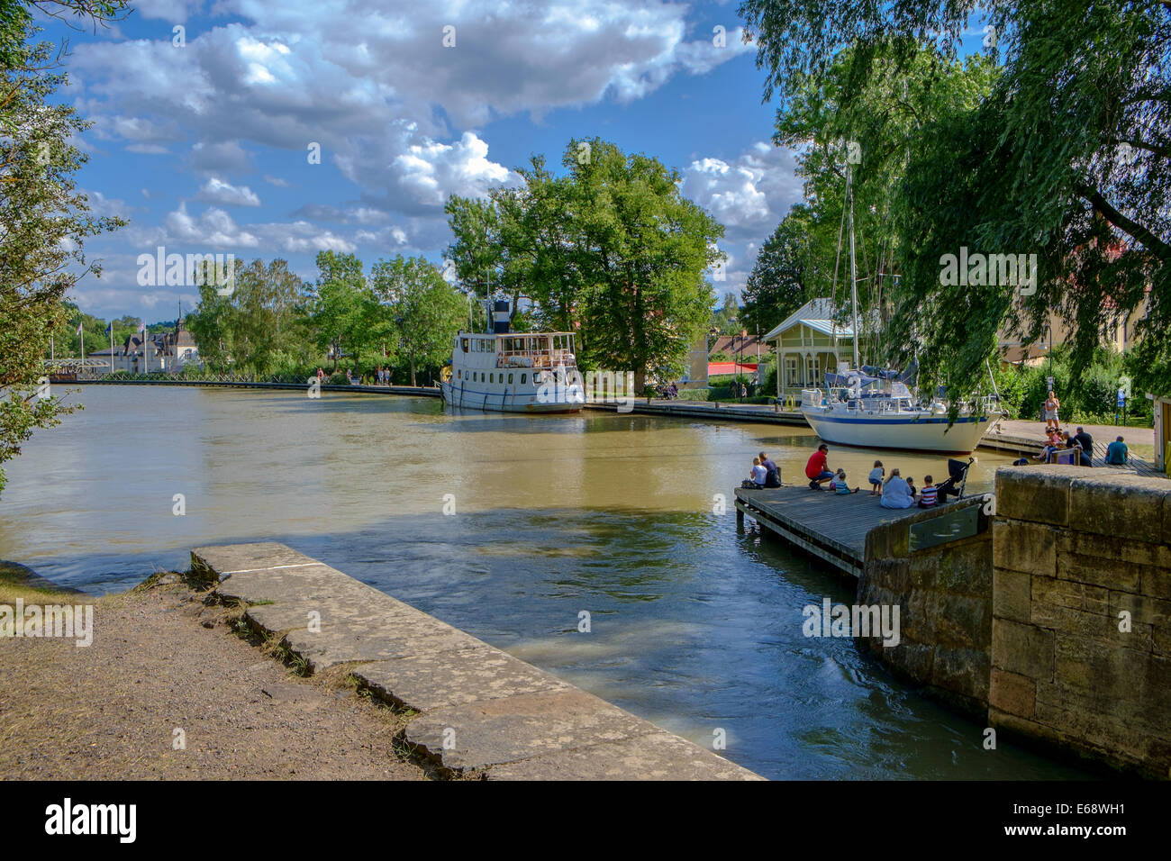 Tourists relax at a lock on Gota Canal in Soderkoping, Sweden. - Stock Image