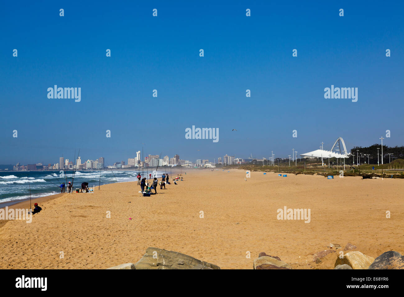 Durban South Africa. Fishermen on the beach with the iconic Moses Mabhida world cup soccer stadium and city of Durban - Stock Image