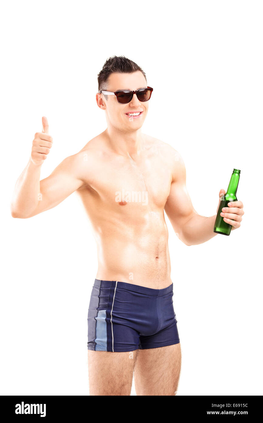 Man in swim shorts holding a beer and giving thumb up - Stock Image
