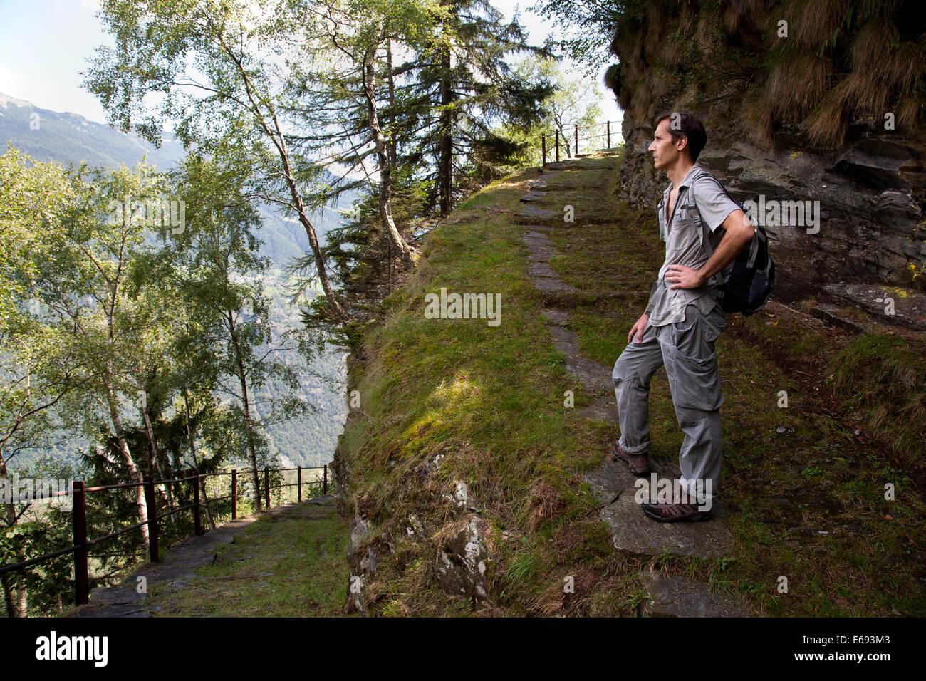Man on mountain path pausing to admire the views. - Stock Image
