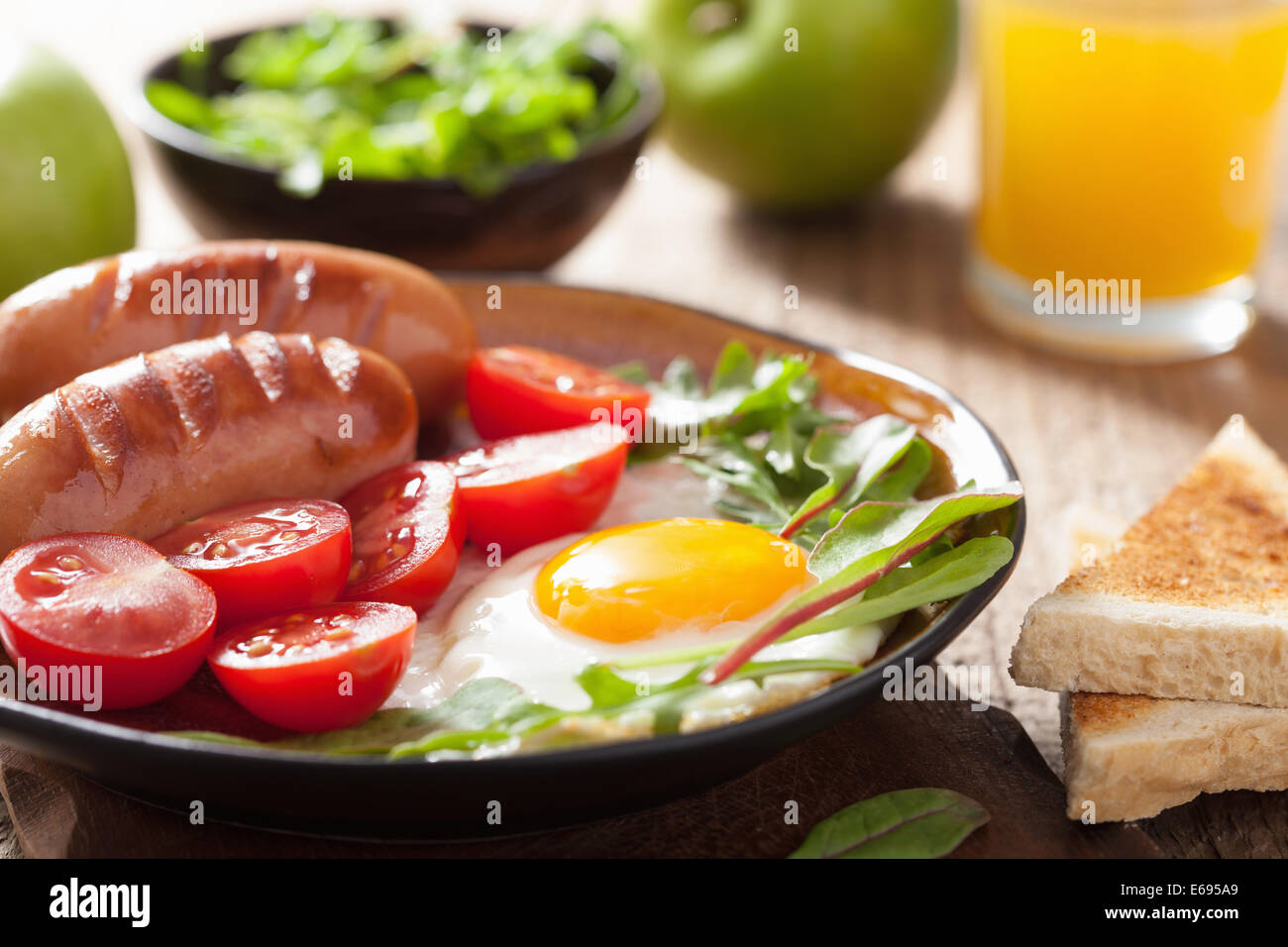 fried egg sausages tomatoes for healthy breakfast - Stock Image