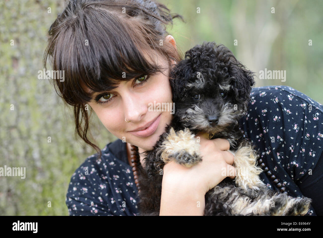 Young woman holding a Toy Poodle or Teacup Poodle, black and tan