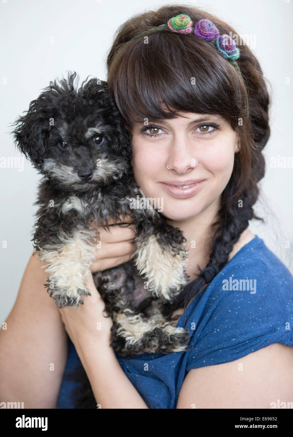 Young woman holding a Toy Poodle, or Teacup Poodle, black