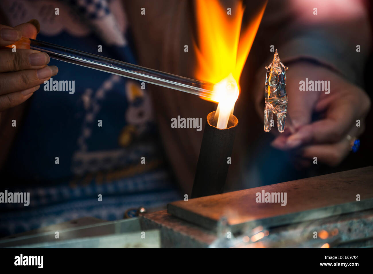 Glassblower working on a glass figure with a flame, Wuzhen, Zhejiang province, China - Stock Image
