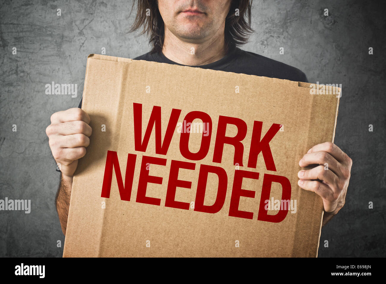 Man needs a job. Unemployed man holding board with title WORK NEEDED - Stock Image