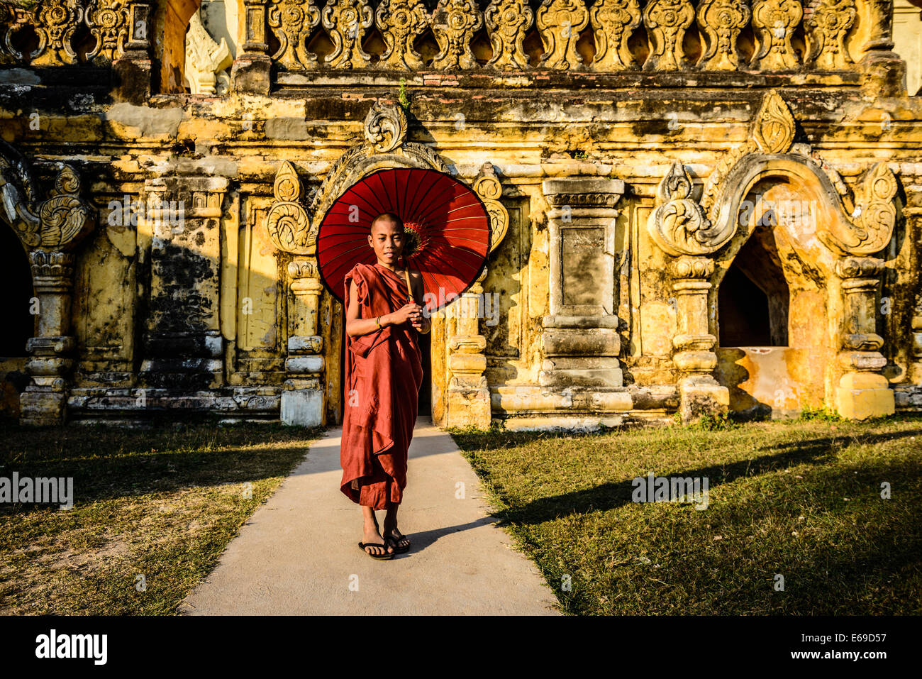 Asian man carrying umbrella by ornate temple - Stock Image