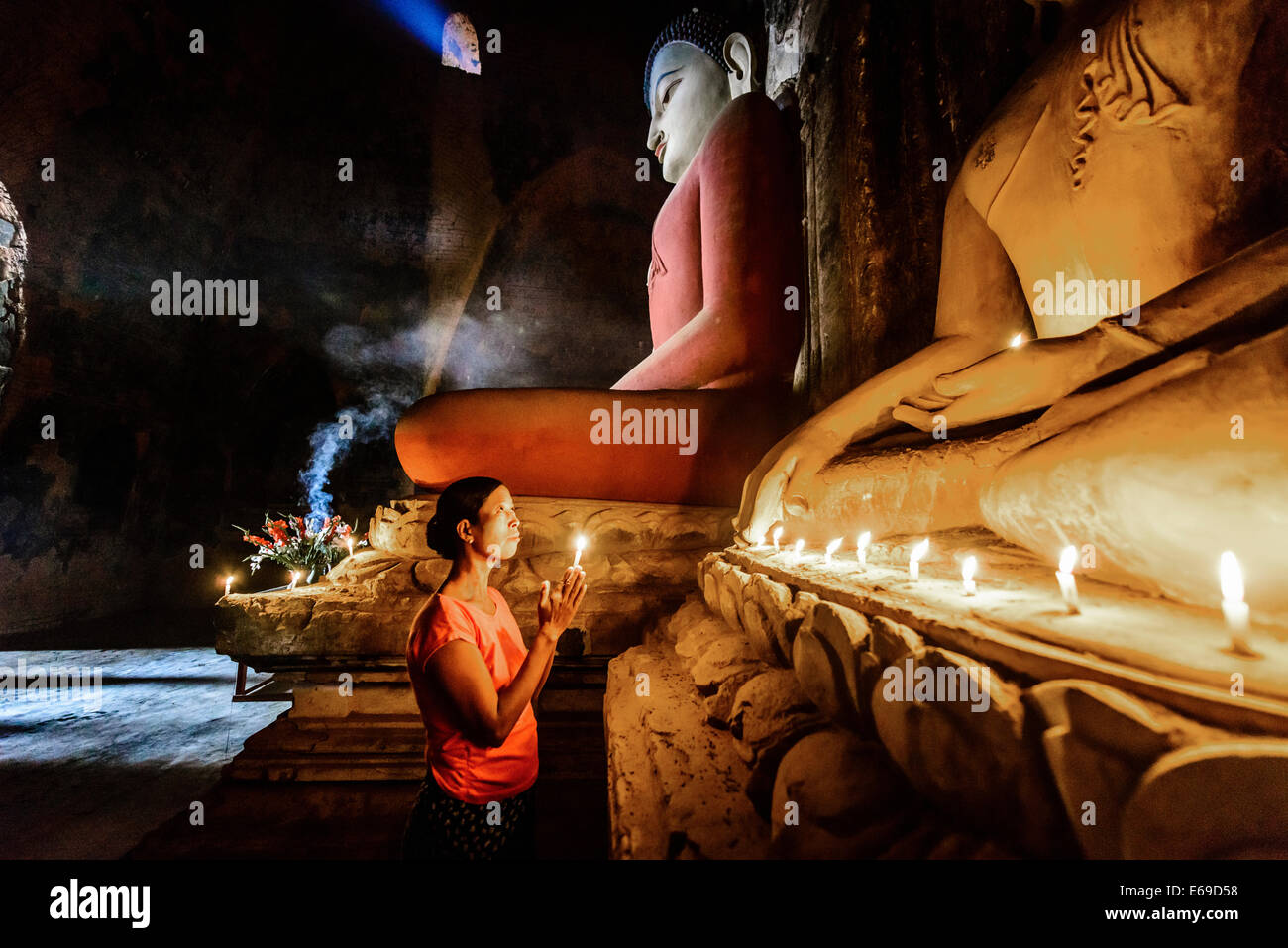 Asian woman lighting candle in temple - Stock Image