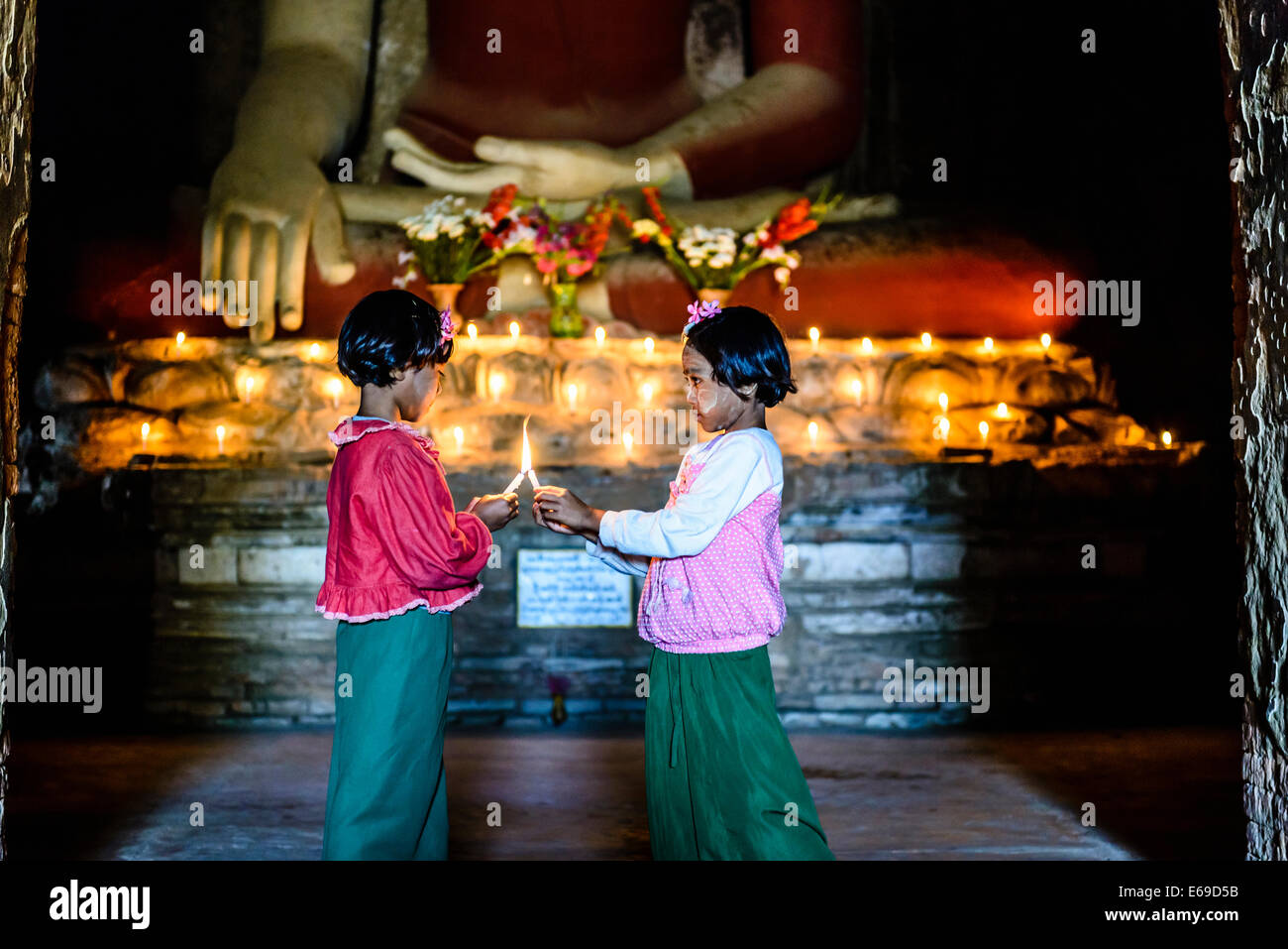Asian girls lighting candles in Buddhist temple - Stock Image