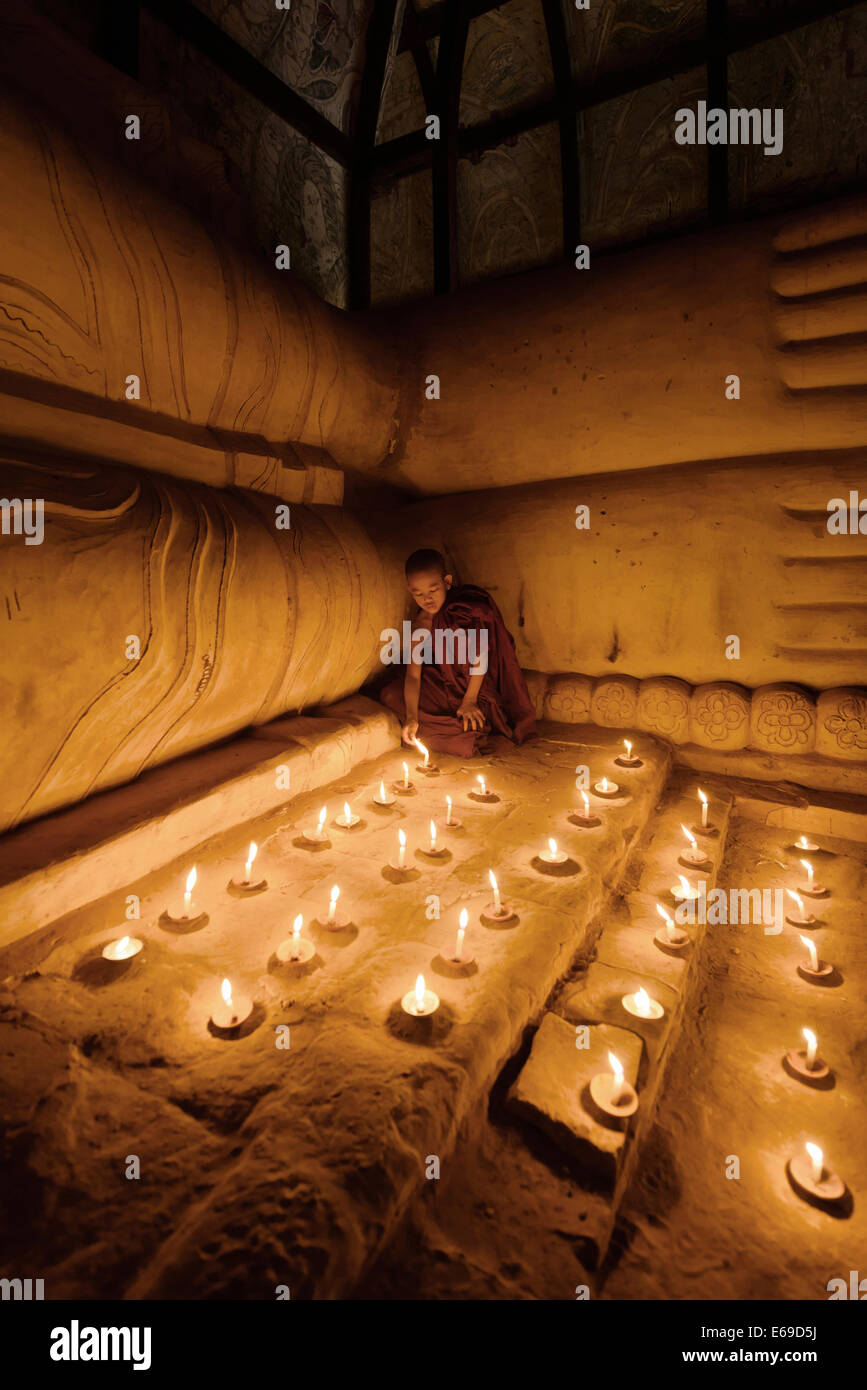 Asian monk lighting candles in temple - Stock Image