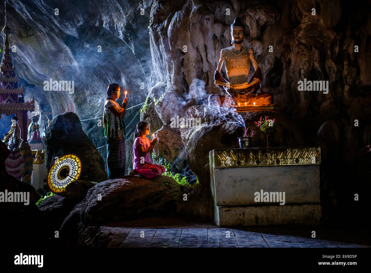 Asian girls lighting incense in temple - Stock Image