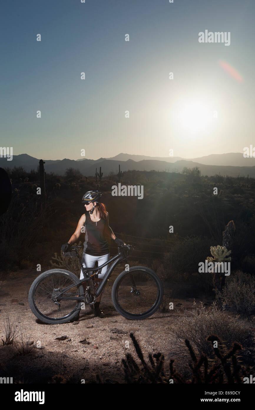Mountain biker standing in desert Stock Photo