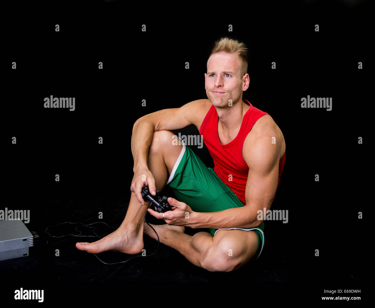 Young man deeply immersed playing a video game while sitting on the floor - Stock Image