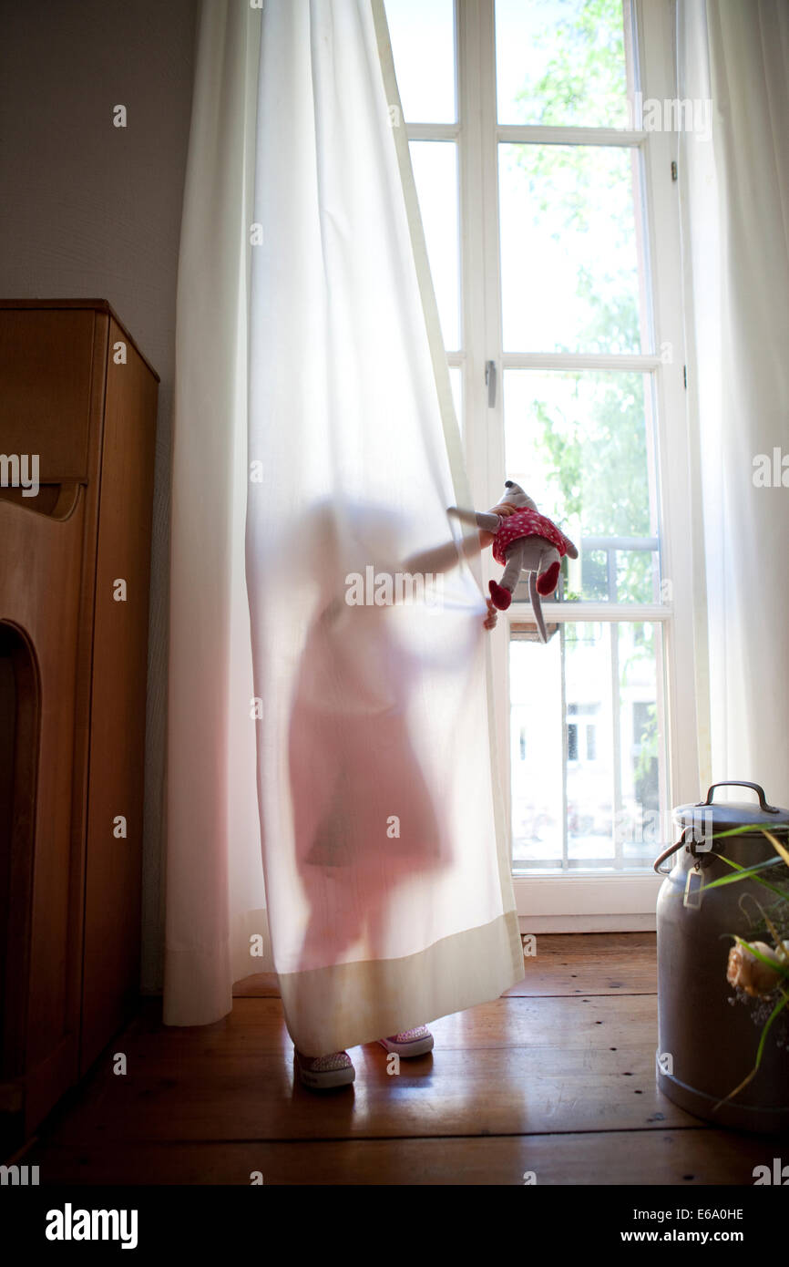 Young girl hiding behind opaque white curtains in a home environment. - Stock Image