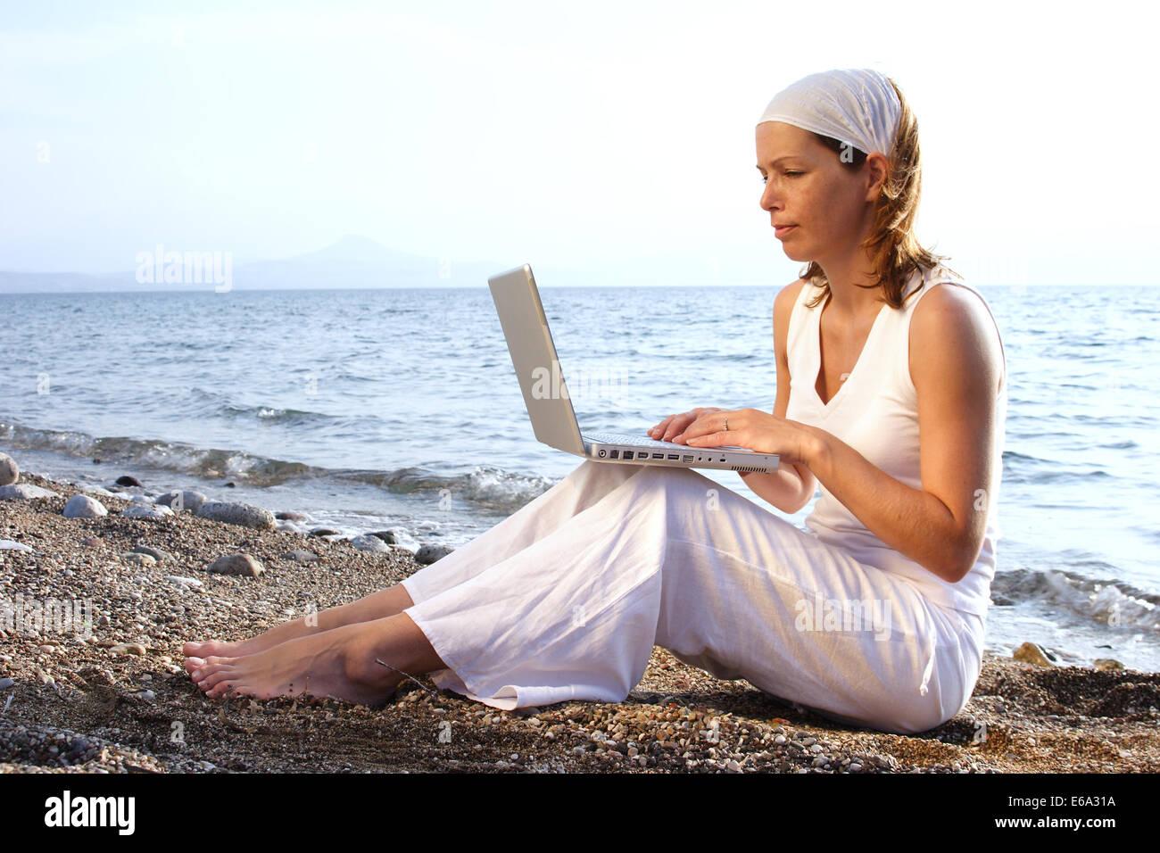 palmtop,young woman,beach - Stock Image