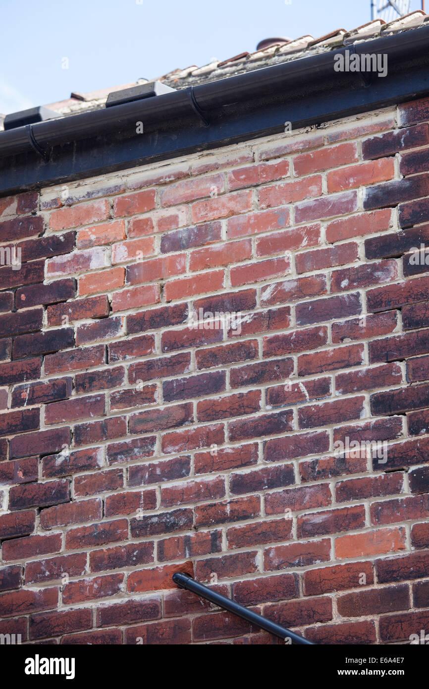 Poor uneven brickwork filling in window on house - Stock Image