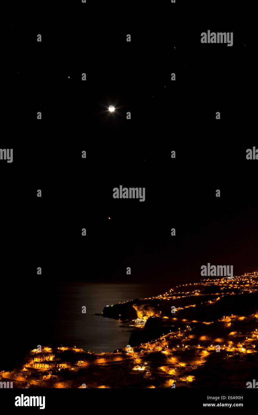 The moon and some bright stars shining over Ribeira Brava. - Stock Image