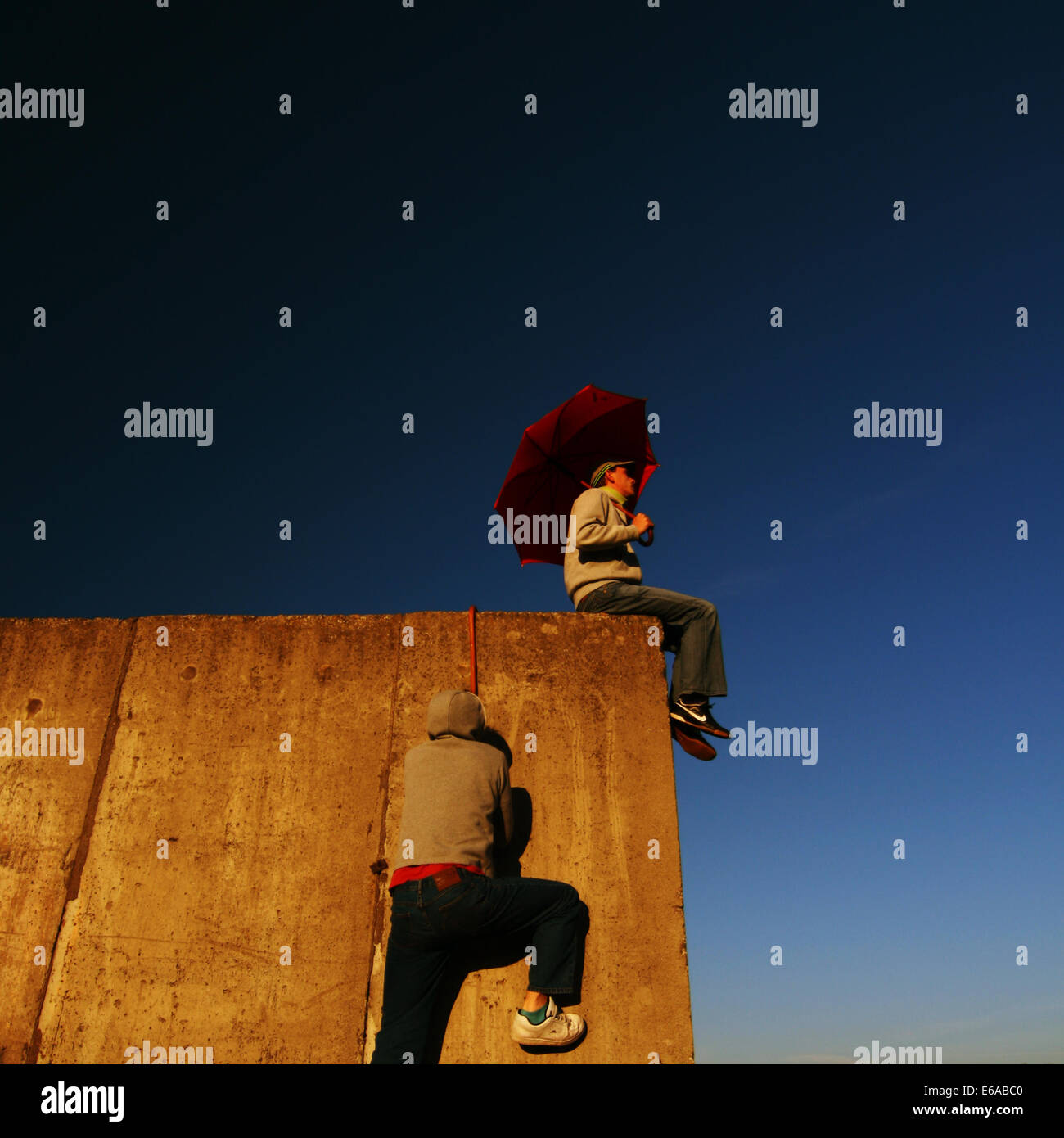 humor,bizarre,wall,climbing,umbrella - Stock Image