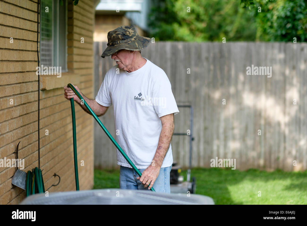 A 76 year old Caucasian man does yard chores by coiling a water hose against the house outdoors. - Stock Image